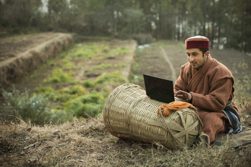 A rural farmer browses the web from a laptop. Global internet access is reducing the geographical constraints on education, employment opportunities, and access to grants.