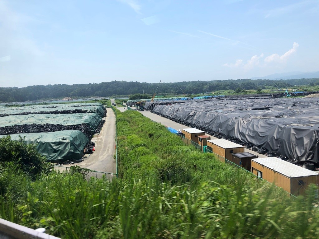 The green and black tarps cover mountains of contaminated topsoil bags. This temporary storage facility is just one of many inside the exclusion zone.