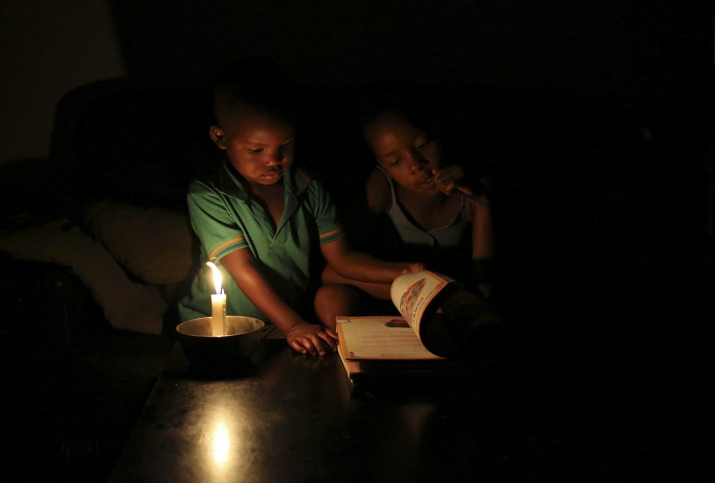 A young boy reads by candlelight