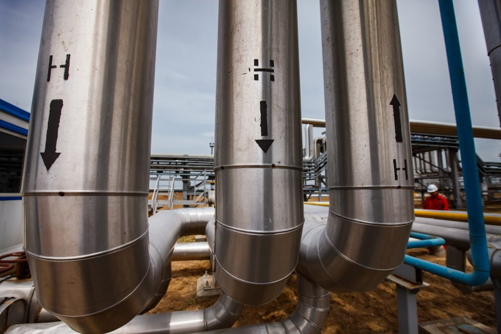 Oil refinery and gas processing plant in desert. Hydrogen sign. Technological tubes and pipelines. Close-up.