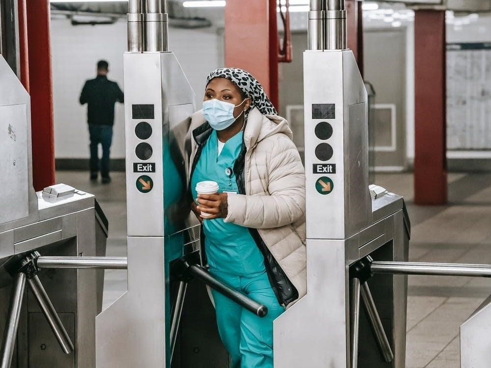 Image credit: Laura James (in the public domain), New York City Nurse passing through a turnstile in the subway station