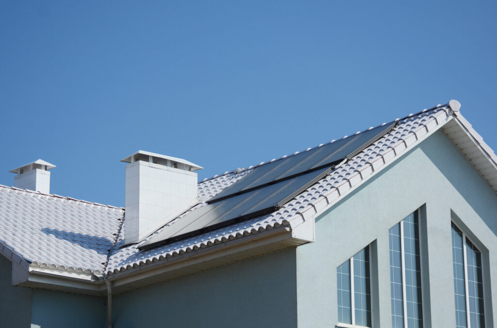 Modern passive house with solar panels and white roof for energy efficiency.