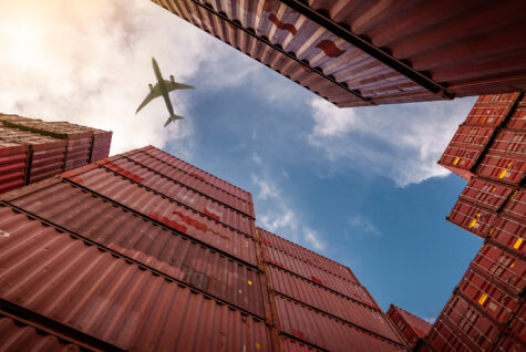 Airplane flying above container logistic. Cargo and shipping business. Container ship for import and export logistic. Logistic industry from port to port. Container at harbor for truck transport.